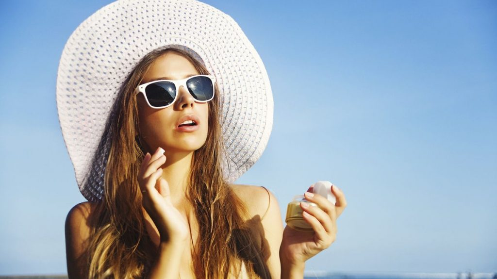 Wearing sunscreen to protect your skin under UV rays